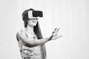 Double exposure. Beautiful woman wearing virtual reality goggles stretching arm. Forest, trees.