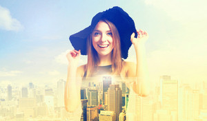 Double exposure of a young happy woman in a hat and a big city skyline