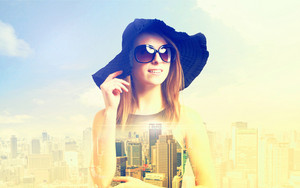 Double exposure of a young woman wearing sunglasses with a big city skyline