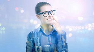 Double exposure of young professional woman in glasses on city background