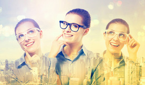 Double exposure of young professional women in glasses on city background