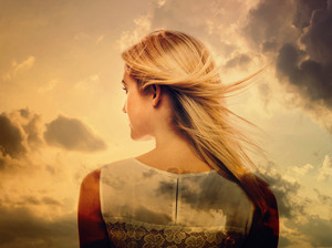 Double exposure of young woman and the sky