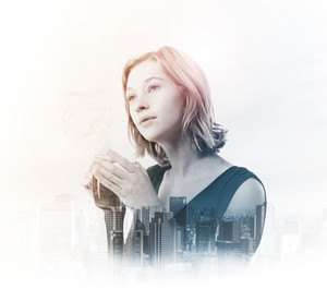 Double exposure of young woman holding tea cup with city buildings