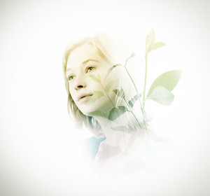 Double exposure of young woman with green leaves