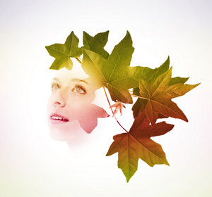 Double exposure of young woman with tree leaves