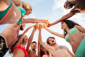 Down view image of a group of happy friends clinking beer bottles standing together in swimwear