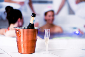 Drinking glass and bottle of champagne in bucket. Bride and happy bridesmaids in bikinis celebrating hen party in jacuzzi in wellness center. Women enjoying a bachelorette party.