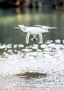 Drone quadcopter with camera flying above water filming or taking pictures. Summer nature.