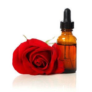 Dropper bottle with beautiful red rose over white background