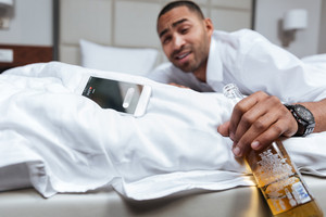 Drunk african man in shirt lying on bed and looking at camera. Focus on bottle