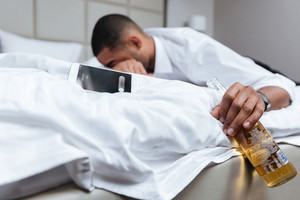 Drunk young african man in shirt sleeping on bed and holding bottle of beer in hand. Focus on bottle. Side view
