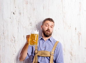 Drunk young man in traditional bavarian clothes holding s mug of beer. Oktoberfest. Studio shot on white wooden background.