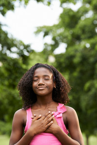 Ecology and environment-Portrait of young african american girl touching her heart in park, smiling and daydreaming with eye closed