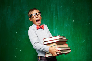 Ecstatic kid holding stack of books while standing by the blackboard and looking at camera