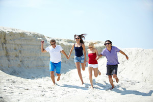 Ecstatic young people running on the sand holding hands