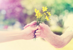 Elderly and young woman holding yellow flowers outside