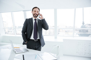 Elderly bearded business man standing with arm in pocket near the table in office and talking at phone