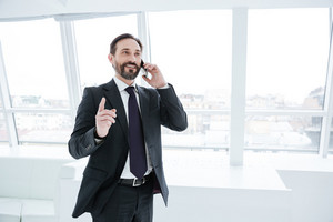Elderly bearded business man talking at phone in office and showing finger up