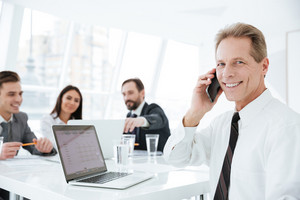Elderly business man in suit sitting by the table in office with colleagues and talking at phone