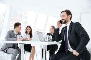 Elderly business man sitting by the table with business partners and talking at phone