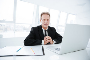 Elderly business man sitting by the table with laptop and documents and looking at camera