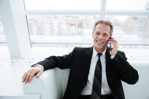 Elderly business man talking at phone and sitting on sofa near the window in office