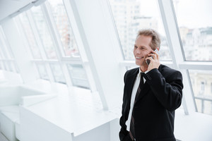 Elderly business man talking at phone and standing near the window in conference room