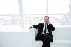 Elderly business man talking on phone and sitting on sofa near the window in office
