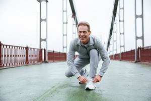 Elderly Runner in sportswear prepare on bridge. Front view