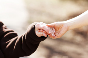 Elderly woman holding hands with young caretaker
