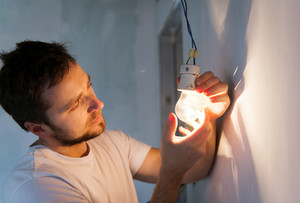 Electrician installing light in a new house