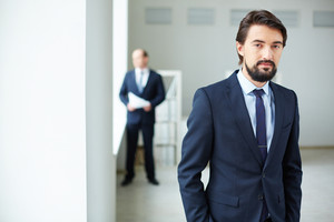 Elegant businessman looking at camera on background of his colleague