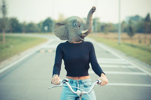 elephant mask young beautiful brunette straight hair woman using bike outdoor