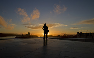 Emotional woman / girl thinking. Standing at a roof in the sunset.
