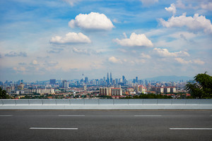 empty asphalt road and cityscape skyline , daytime scene