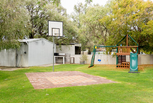 Empty basketball court and kids playground on garden