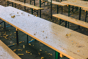 Empty beer garden in fall without guest due to rainy weather. Empty table and benches