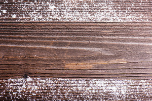 Empty brown wooden background with white  powder on it. Studio shot.