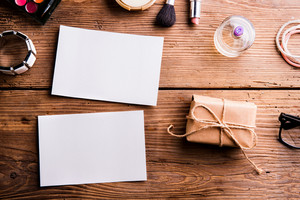Empty paper notes, little package and various make up products. Studio shot on wooden background. Copy space, flat lay.