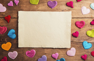 Empty paper sheet and colorful fabric hearts. Studio shot on wooden background.