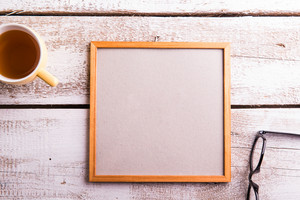 Empty picture frame, eyeglasses and cup of tea. Studio shot on white wooden background. Flat lay, copy space.