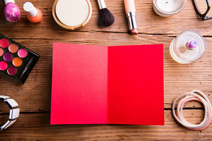 Empty red greeting card laid on table. Various make up products. Studio shot on wooden background. Flat lay, copy space.