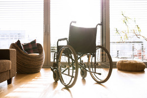 Empty wheelchair in sunny living room next to the couch