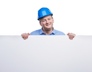 Engineer in blue hard hat holding a blank sign board. Studio shot on white background.