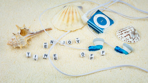 Enjoy time off letters between sea shells and audio player on sandy beach