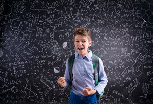 Excited and victorious boy against big blackboard with mathematical symbols and formulas