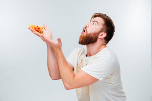Excited bearded man holding slice of pizza on his palms isolated on white background