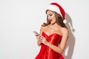 Excited brunette woman in red santa claus dress holding mobile phone isolated on the white background