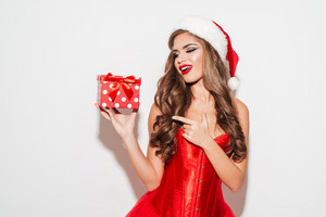 Excited brunette woman in red santa claus outfit pointing finger at small gift box isolated on the white background