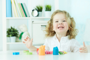 Excited child enjoying her favorite hobby – playing with modeling clay
